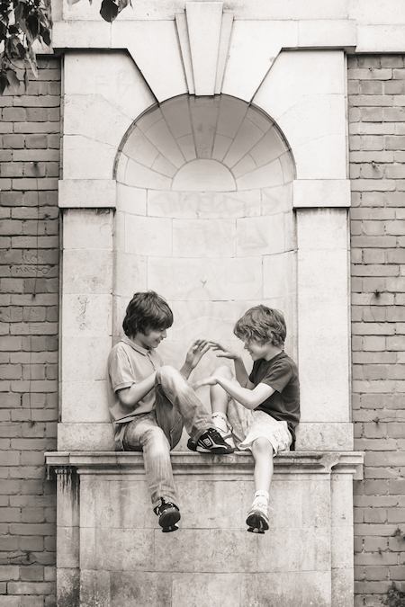 Brothers sitting in alcove playing